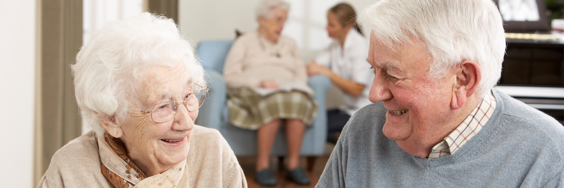 elderly couple smiling with patient in background